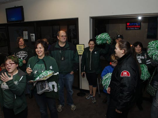 About 20 Spartan football fans greet the MSU Spartan football team, who arrived at Lansing's Capital Region International Airport Friday afternoon.