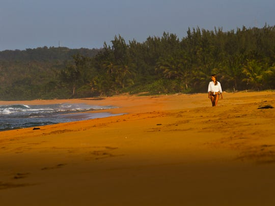 A lone visitor explores the golden sands of Playa La