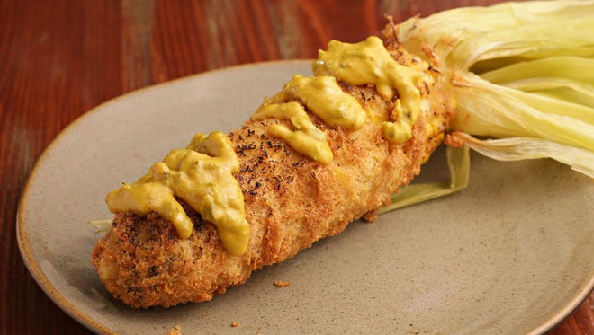 Deep fried cornbread crusted corn on the cob with jalapeño mustard by chef Bryan Dooley.