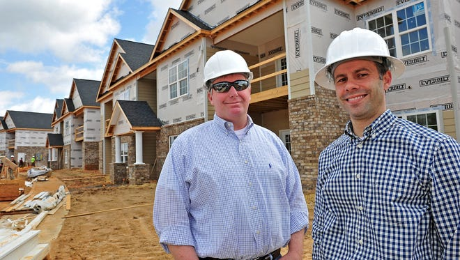 Dean Montgomery, left, and Bryan Little pose for a photograph in front of the apartment complex at the Standard Apartments site in White House, Tenn., Wednesday, April 22, 2015.