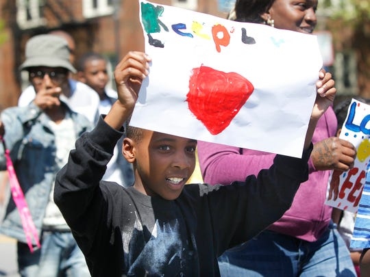 """Treyvon Brown, 8, of Rochester holds a sign that says """"Keep Love"""" during the walk."""