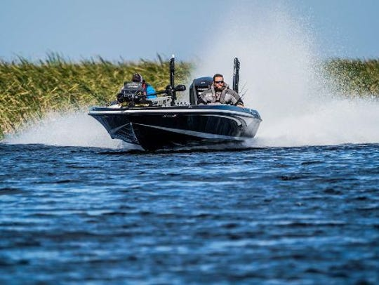 A bass boat runs wide open on Lake Okeechobee during the first day of competition in the FLW Tour presented by Evinrude at Clewiston.