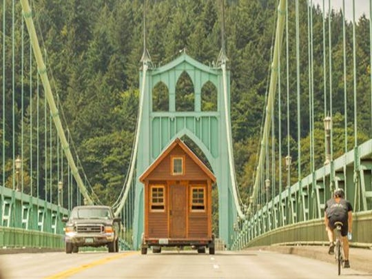 Johnathan William's tiny house crosses a bridge in Portland, Oregon, on its journey to Colorado, where it became his home at the base of a mountain.