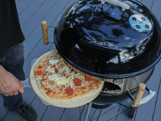 Slide a pizza into a charcoal grill