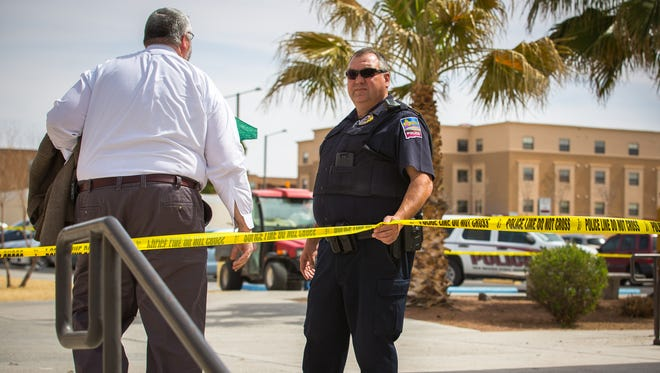 New Mexico State University Police Lieutenant Richard McGuinn, right, assists a man as he walks through an area with an active beehive at the northeast corner of the Garcia Annex on campus. The area was marked off with caution tape after a report was made of bees being aggressive in the area.