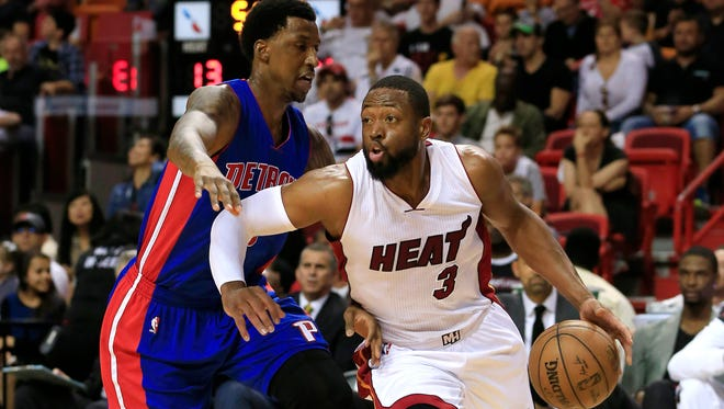 Miami Heat guard Dwyane Wade dribbles the ball as Detroit Pistons guard Kentavious Caldwell-Pope defends in at American Airlines Arena.