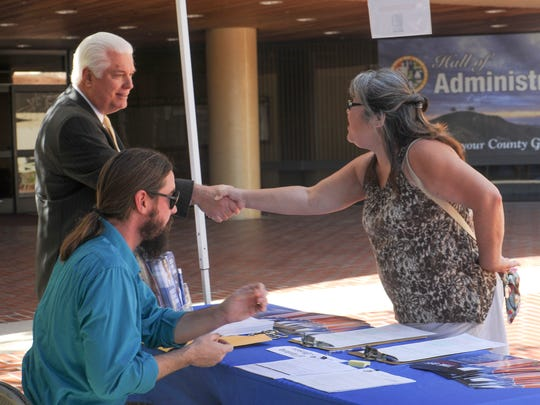 Mark Lunn, left, the county clerk and recorder, shakes hands with Debra Salem-Drake, of Ventura, as Jason Quillan, a records technician in his office, helps her Tuesday with a mail-in ballot at the Ventura County Government Center in Ventura.