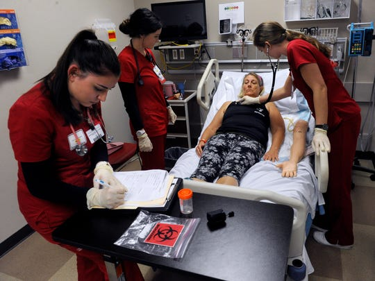 """Former Texas Tech nursing students Pamela Terrazas (left), Mikena Madera and Annie Means work on """"patient"""" Brenda Stremmel during a simulated Trauma Day in February 2018, which provided students from multiple Texas Tech University Health Sciences Center departments a hospital environment. Students were faced with 41 different scenarios. The education process has changed drastically under coronavirus precautions."""