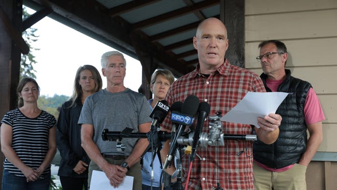 Mike Mathews and friends of Richard Russell talk to the media Saturday, Aug. 11, 2018, at the Orting Valley Police and Fire Department, in Orting, Wash. Russell is presumed dead after stealing a plane from SeaTac International Airport and crashing it into Ketron Island Friday, Aug. 10. (Bettina Hansen /The Seattle Times via AP)