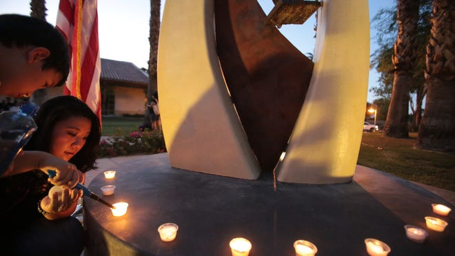 Charlotte Radi and her son Max Radi, 5, light candles around the Never Forget 9-11-2001 memorial during a 9/11 vigil on Thursday at La Quinta Civic Center Park.<137> , September 11, 2014<137>
