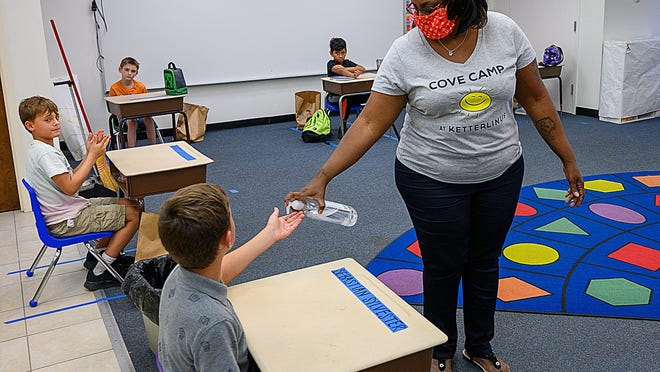 Ketterlinus Elementary School Summer Extended Day Program assistant camp director gives a student hand sanitizer in a classroom.