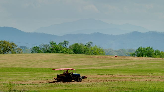A farmer rests on his tractor in a field during a hot afternoon in Alcoa, Tennessee on Saturday, April 15, 2017.