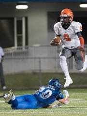 Lely quarterback Jacquez Carter hurdles Kevin Thorne of Barron Collier during the game at Barron Collier Friday night, September 23, 2016. Photo by Darron R. Silva