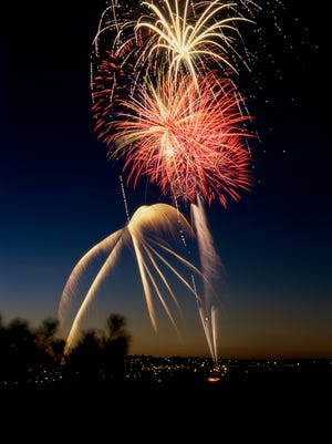 Low angle view of fireworks display at night in a city