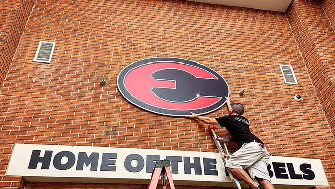 A worker installs a new sign to welcome everyone who comes into Effingham County High School. School starts Aug. 5.