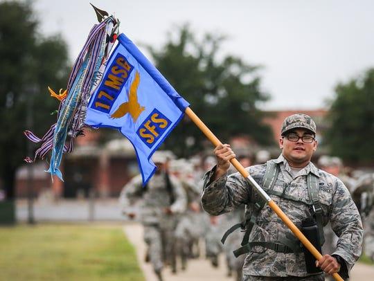 Airman 1st Class Adrian Varela carries a flag during