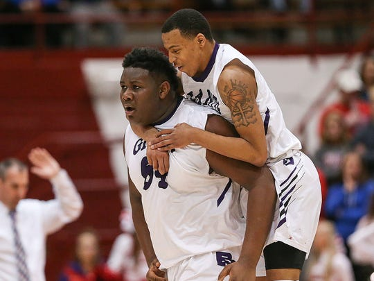 Ben Davis' Dawand Jones leaves the court for a timeout as teammate Jalen Windham jumps on his back to celebrate.