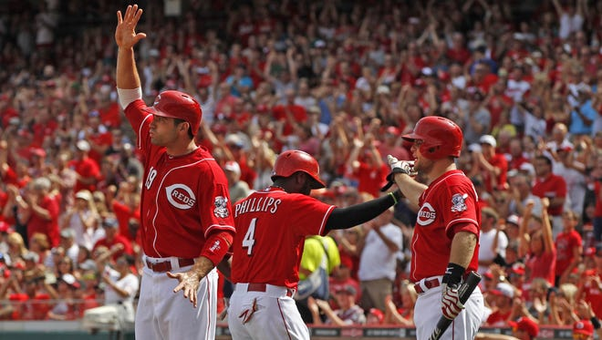 Cincinnati Reds first baseman Joey Votto (19), left, and Brandon Phillips (4), center, celebrate with Devin Mesoraco (39) after scoring on a single by Ryan Ludwick, off Toronto Blue Jays starting pitcher J.A. Happ (48) during the first inning.