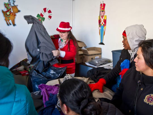 Lori Marie Ciello, a volunteer from the Monmouth County Sheriffs office distributes coats for those in need. The Asbury Park Toy Drive takes over a vacant storefront in downtown Asbury Park as hundreds of people line up for gifts, clothing, and food.