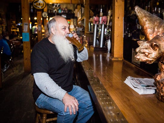 Owner Stan Stephens has a drink at his bar, The Heorot,