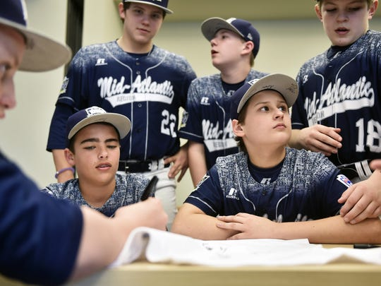 "Members of the Red Land Little League team, including, from second from left, Camden Walter, Cole Wagner, Jarrett Wisman, Adam Cramer and Dylan Rodenhaber, sign a T-shirt Wednesday, March 23, 2016, at the Grace Milliman Pollock Performing Arts Center in Camp Hill. Movie producers Jameson Hesse and A.J. Ferrara announced they will begin production of a feature film based on the Red Land Little League team that won the Little League World Series U.S. Championship in 2015. The film, titled ""Against the Odds,"" will rely on fundraising and will be filmed in the area, with a portion of the profits going toward a new youth baseball complex for Red Land Little League."