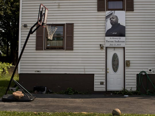 A photo of a victim of gun violence hangs over the entrance to a home in the South Side neighborhood of Syracuse, N.Y., on Aug. 21.