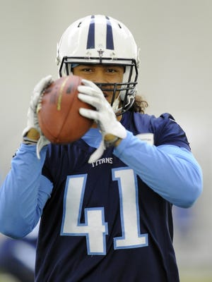 Titans outside linebacker J.R. Tavai pulls in a catch during practice on June 2, 2015, in Nashville, Tenn.