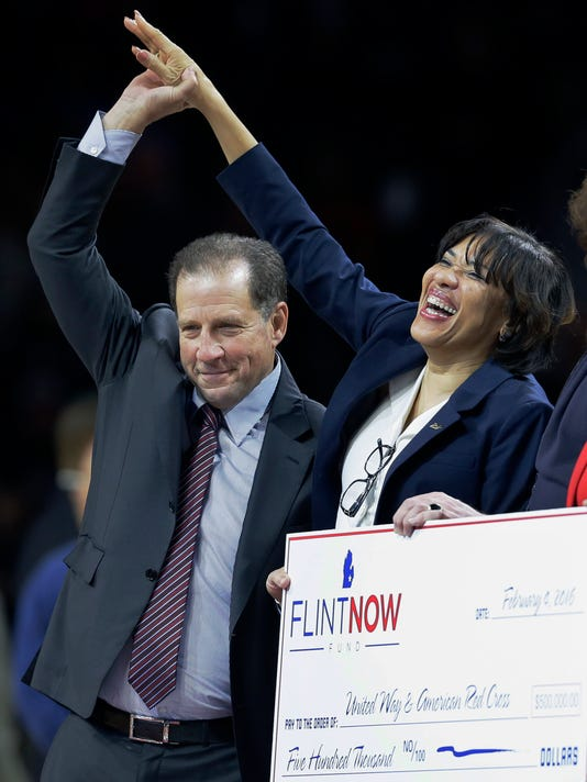 Detroit Pistons/Palace of Auburn Hills vice chairman Arn Tellem, left, holds up Flint, Mich., Mayor Karen Weaver's hand during a presentation of a check from the Pistons to the city during the first half of an NBA basketball game, Thursday, Feb. 4, 2016 in Auburn Hills, Mich. (AP Photo/Carlos Osorio)