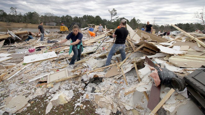 Friends and family members help clean up where the home of Darrel and Kristy Shows once stood in Collinsville, Miss., Wednesday, Feb. 3, 2016. Lauderdale County Sheriff Billy Sollie said the tornado damaged homes, toppled trees and knocked out power.