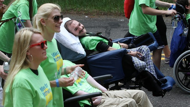 Family and friends accompany residents of the Matheny Educational and Medical Center through the streets of Peapack-Gladstone in the 2015 Lu Huggins Wheelchair Walk.
