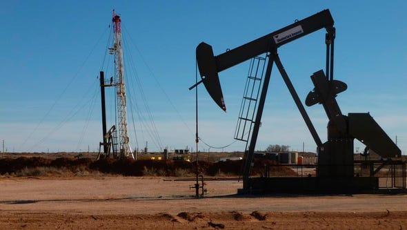 A drilling rig operates near a pump jack in Eddy County.