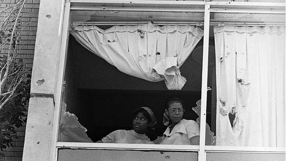 Two Jackson State University students stare out a dormitory window shot out by law enforcement officers on May 14, 1970.