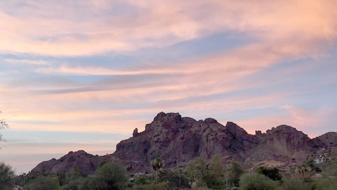 The morning sky brightens as the sun rises over Camelback Mountain as seen in this photograph from Paradise Valley resident.
