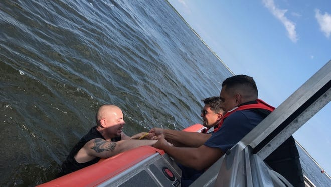 A Coast Guard boat crew pull a man aboard their vessel who fell from a capsized Jon boat.