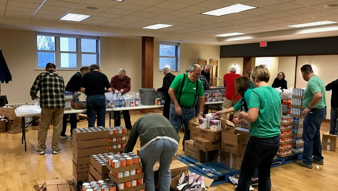 Volunteers pack food for Weekend Survival Kits, which will be sent home in children's backpacks to ensure they have meals when not in school.