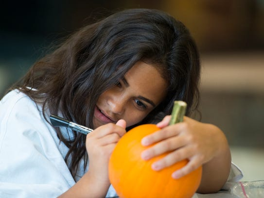 Samantha Ortiz, 8, of Hershey decorates a pumpkin