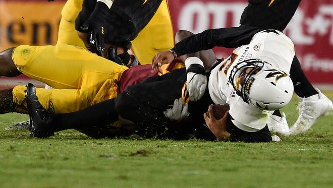 Arizona State Sun Devils quarterback Manny Wilkins (5) is tackled by Southern California Trojans defensive tackle Rasheem Green (94) and injured on the play during the first half at Los Angeles Memorial Coliseum.