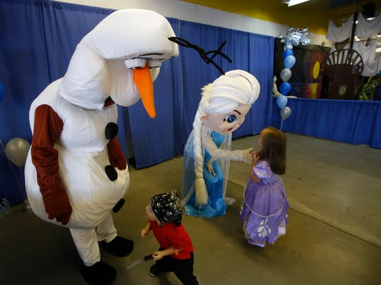"Hayden Mansker, left, and Hayleigh Mansker play with characters Olaf and Elsa from the movie ""Frozen"" Saturday during KidFest at McGee Park."