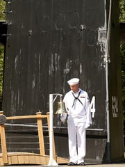 The sail of the USS Woodrow Wilson looms in the background as Mason Bucher, a sailor aboard the USS Corpus Christi, rings the bell.