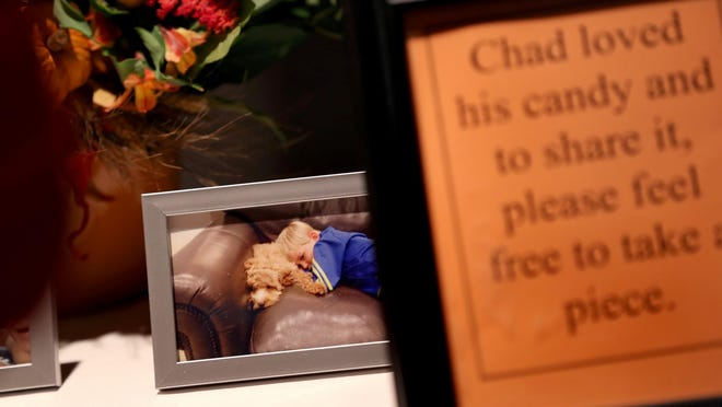 A photo of Chad Carr sat a table with a basket of candy during the visitation and memorial service, a Celebration of Life for Charles (Chad) Clinton Carr at Saline High School Performing Arts Center in Saline Mi., on Sunday, November 29, 2015. Chad Clinton Carr passed away November 23, 2015 after a 15-month valiant battle with Diffuse Intrinsic Pontine Glioma.