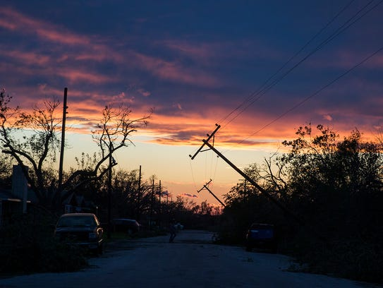 Power poles blown by Hurricane Harvey lean over a road