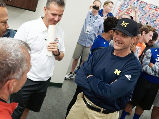 June 12, 2015: Jim Harbaugh, right, the University of Michigan's head football coach speaks with Urban Meyer, center, The Ohio State University's head football coach, and other coaches at the Sound Mind Sound Body Football Camp at Dakota High School in Macomb.