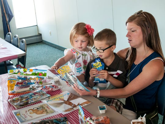 Brittni Fenton, of Burtchville Township, reads a book to her children, Ella Fenton, 4, and Lucas Fenton, 6, during Meet Up and Eat Up Wednesday, June 21, 2017 at the St. Clair County Library in Port Huron. The program offers free lunch and breakfast to children under 18 at more than a dozens sites.