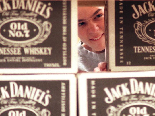 Chris Baumhoer, 13, stacks decorative Jack Daniel's