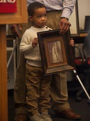 Maxim Moore, age four, stands next to his father Derek Moore, holding a photograph of his great, great, great, great grandfather Henry Mathis who was a slave in 19503. The Moore's were part  of an unveiling monument ceremony recognizing New JerseyÕs slave trade. The event took place at the Rutgers Camden University in the Walt Whitman Building.