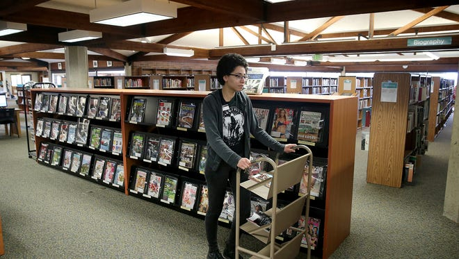 Kitsap Regional Library, Central Branch Library in Bremerton associate Jessica Staples puts out magazines on Friday.
