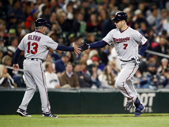 Minnesota Twins first baseman Joe Mauer (7) is greeted by third base coach Gene Glynn (13) following his solo homer on Friday against the Seattle Mariners at Safeco Field in Seattle.