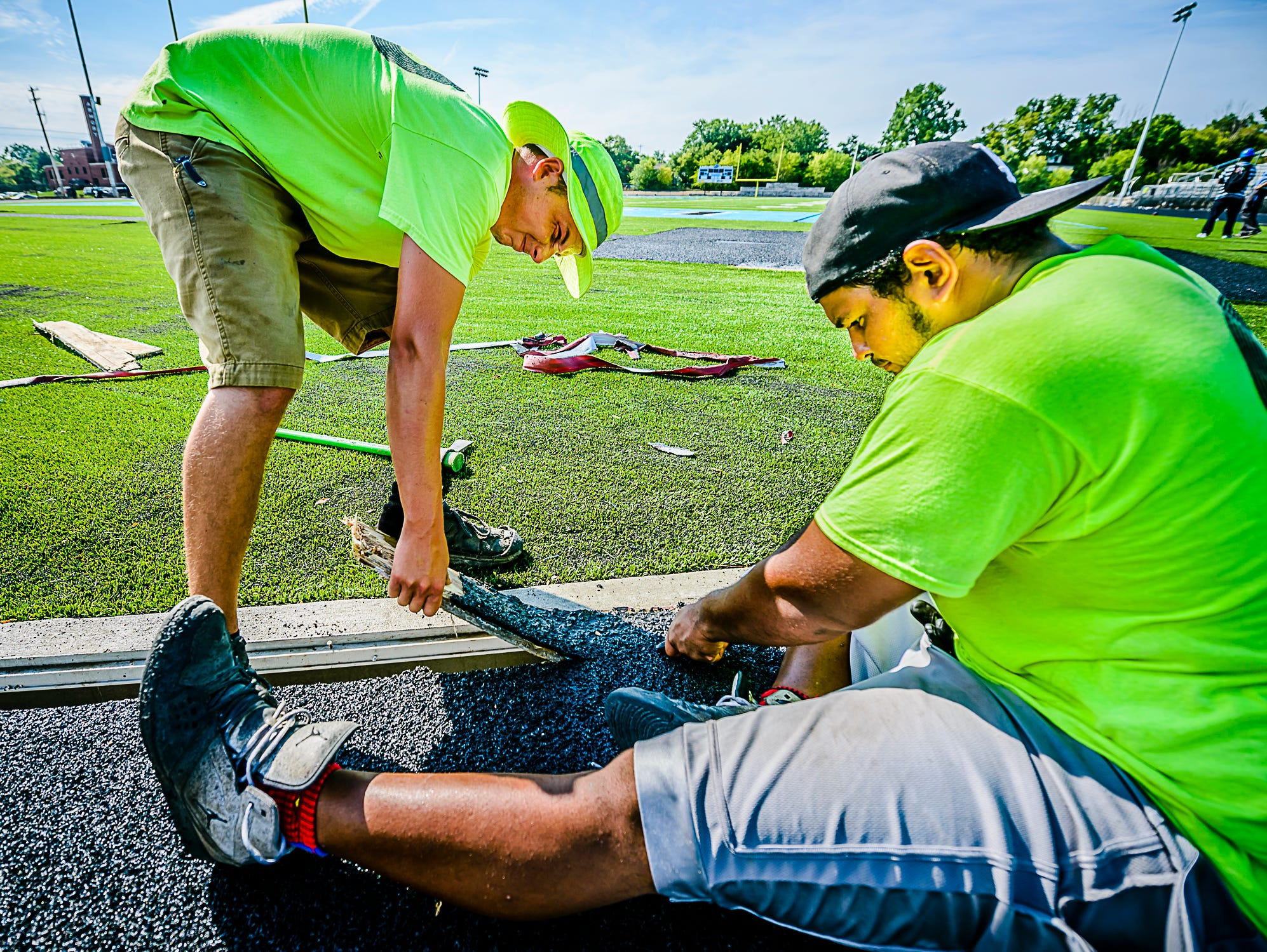 Michael Wheaton ,left, and Jeff Drye remove the extra wood that covers the drains between the new track and the football field at Lansing Catholics' new stadium.