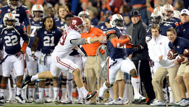 Auburn Tigers cornerback Chris Davis (11) gets past Alabama Crimson Tide punter Cody Mandell (29) and scores a 100 yard touchdown during the fourth quarter at Jordan Hare Stadium in 2013. Auburn won 34-28.