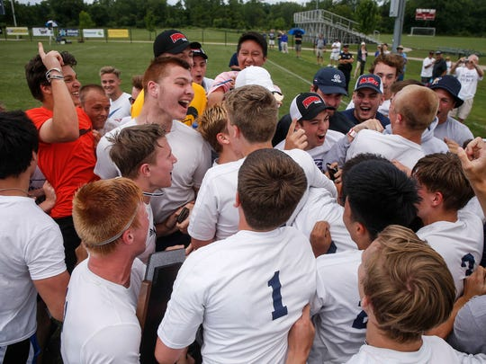 Members of the Iowa City Regina boys soccer team celebrate a 2-1 win over Des Moines Christian in the Class 1A state boys soccer championship game in Des Moines on Saturday, June 2, 2018.
